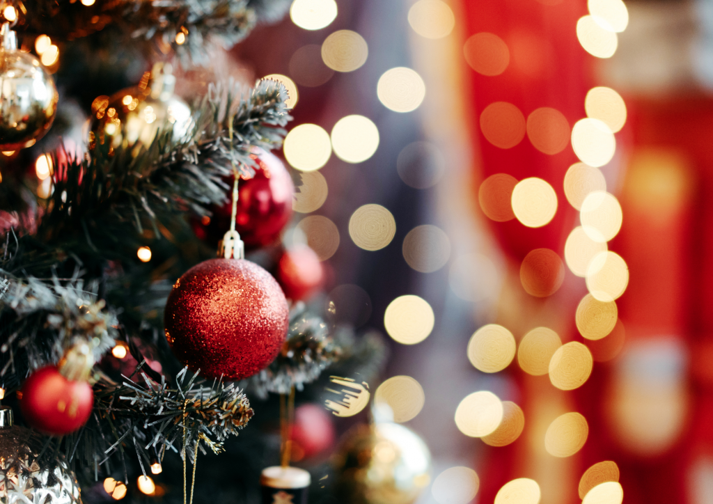 Close up picture of a Christmas tree with red baubles in the forefront