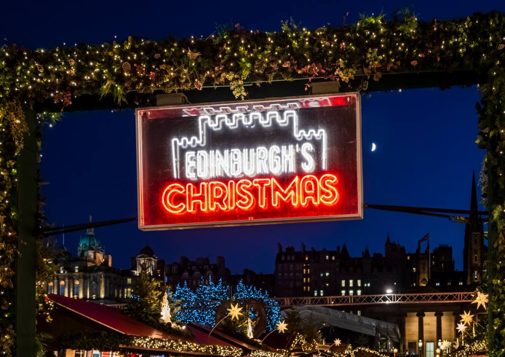 Photo of Edinburgh's Christmas market sign with the Old Town in the background