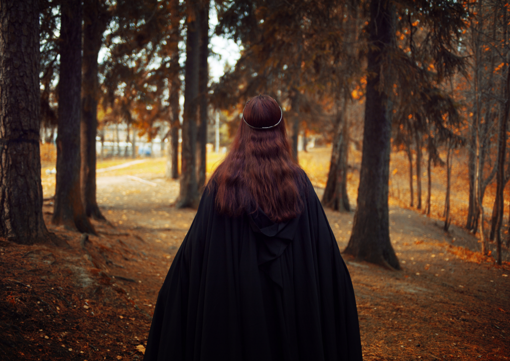 The back of a woman walking through a wood wearing a black cloak and looks a bit like a witch.