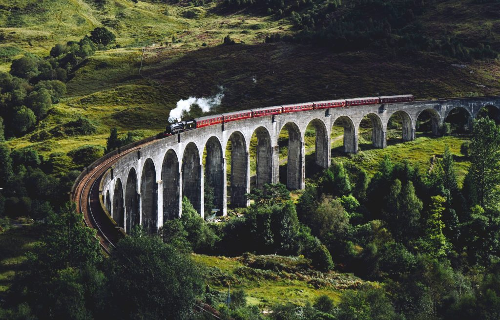 An image of The Glenfinnan Viaduct and Jacobite Express. The train is going over the viaduct and the background is full of green vegetation.