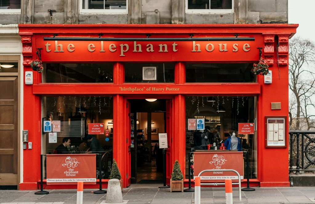 Image of The Elephant House on George IV Bridge in Edinburgh. It has a bright red front and says birthplace of Harry Potter on the sign.